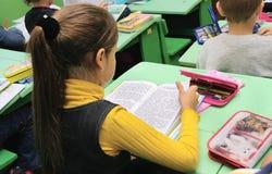Omsk, Rusia - 24 de septiembre de 2011: el tercer graduador de la muchacha lee el libro en el escritorio de la escuela Imagen de archivo