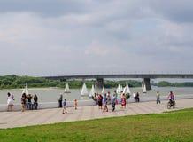 Omsk, Rusland - Augustus 04, 2013: De dijk van de Irtyshrivier met mensen, mening van de brug van Leningrad Stock Fotografie