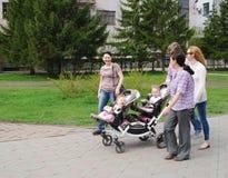 OMSK, RUSLAND - MEI 09, 2015: gelukkige familie met jonge geitjestweelingen op gang Stock Afbeeldingen