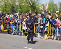 Omsk, Russia - May 09, 2014: public event, crowd of people behind fence and policeman Stock Image