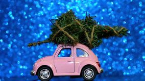 Omsk, Russia - Oktober 27, 2018: Toy model car with Christmas tree on on the roof rides on Blue Blurred Glitter background. Christ. Mas Delivery stock video footage