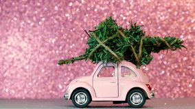 Omsk, Russia - Oktober 27, 2018: Toy model car with Christmas tree on on the roof rides on pink Blurred Glitter background. Omsk, Russia - Oktober 27, 2018: Toy stock footage