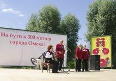 Omsk, Russland - 12. Juni 2015: Ensemble von Veteranen singen Lied auf Szene im Freien Stockfotos