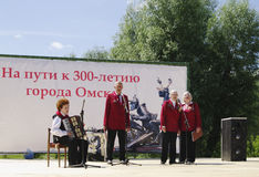 Omsk, Russland - 12. Juni 2015: Ensemble von Veteranen singen Lied auf Szene im Freien Lizenzfreies Stockfoto