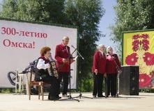 Omsk, Russland - 12. Juni 2015: Ensemble von Veteranen singen Lied auf Szene im Freien Stockfotografie