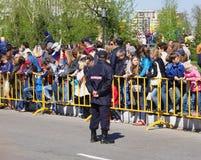 Omsk, Russland - 9. Mai 2014: allgemeines Ereignis, Menge von Leuten hinter Zaun und Polizist Stockbild
