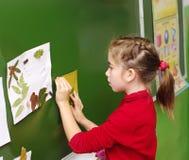 Omsk, Russland - 24. September 2011: Mädchen hängt Blatt mit Applikation auf Schulbehörde Lizenzfreie Stockbilder