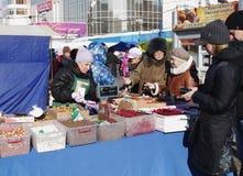 Omsk Ryssland - mars 07, 2015: säljare och köpare på räknaren av den utomhus- marknaden Royaltyfria Foton