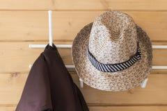 Omslag och hatt som hänger på hängaren i hallet royaltyfri bild