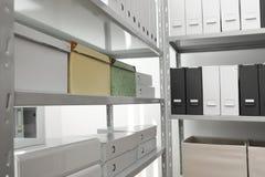 Omslagen en vakjes met documenten op planken stock foto