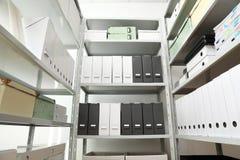 Omslagen en vakjes met documenten op planken stock foto's