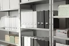Omslagen en vakjes met documenten op planken stock afbeelding