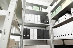 Omslagen en vakjes met documenten op planken in archief stock afbeeldingen