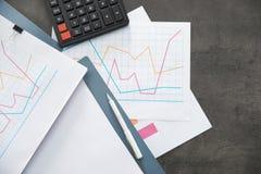 Omslagen met documenten en calculator op bureaulijst stock afbeelding