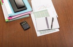 Omslagen met documenten, grafieken, rapporten, calculator en pen op een Desktop Stock Foto