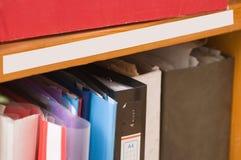 Omslagen met documenten op een plank. Stock Afbeeldingen