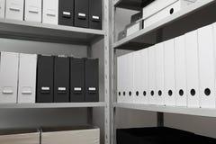 Omslagen met documenten op planken stock afbeeldingen