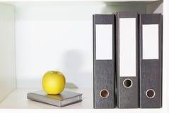 Omslagen voor documenten, ontwerper en groene appel op een boekenplank Royalty-vrije Stock Foto