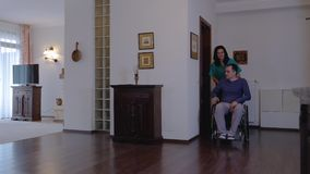 Omsorgarbetare med den unga mannen i rullstol hemma stock video