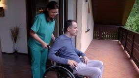 Omsorgarbetare med den unga mannen i rullstolen som kommer på terrassen arkivfilmer