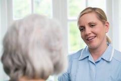 Omsorgarbetare som hemma talar till den höga kvinnan royaltyfria bilder