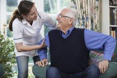 Omsorgarbetare som hjälper den höga mannen att få upp ut ur stol Arkivbild
