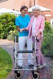 Omsorgassistent som hjälper en äldre dam Arkivfoto
