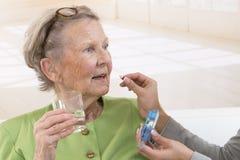 Omsorgdonator eller sjuksköterska som ger till den äldre kvinnan hennes preventivpillerar Fotografering för Bildbyråer