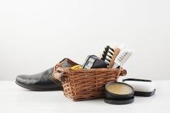 Omsorgskor och mäns svarta skor på vit Arkivfoto