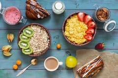 Omväxlande sund frukost på en blå lantlig bakgrund Havreflingor, jordgubbar, mysli, kiwin, mandlar, mjölkar, bärmousse som bakas royaltyfria bilder