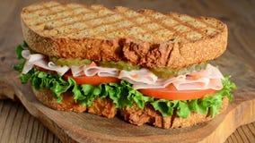 Omwenteling van de smakelijke sandwich van Turkije met tomaat, salade en komkommer, op houten achtergrond stock footage