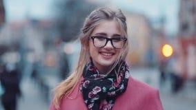 Omwentelings dichte omhooggaande mening van het jonge meisje mooie glimlachen naar de camera Gelukuitdrukking Modieus kijk positi stock videobeelden