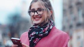 Omwentelingsmening die van een mooi modieus meisje die haar smartphone voor Internet gebruiken die, dan naar de camera kijken sur stock footage