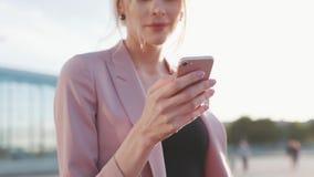 Omwentelingsmening van een mooie blondevrouw in een roze jasje die haar celtelefoon voor het texting in een heldere zonneschijn m stock videobeelden