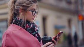 Omwentelingsmening van een schitterend modieus meisje die een kop van koffie houden en haar telefoon voor Internet-het surfen met stock video