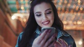 Omwentelingsmening van schitterend donkerbruin meisje gebruikend haar cellphone en glimlachend aan het scherm door de clubingang  stock videobeelden