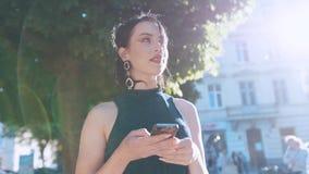 Omwentelingsmening van schitterende modieuze jonge vrouw die Internet via smartphone surfen terwijl status in overvol stock videobeelden
