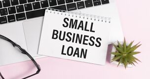 Free On A Light Blue Background Lie Black Glasses And A Pen, White Glasses And A Notebook With The Words SMALL BUSINESS LOAN. Stock Image - 214341521