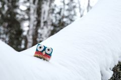 On A Snow Fallen Tree In The Forest In The Winter Is A Toy Homemade Owl Stock Photography