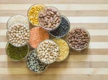 被分类的扁豆和豆类在玻璃碗, ona砧板 免版税库存照片