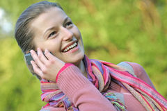 Ona a phone in the park. A young attractive girl talking on a phone while strolling in the park Royalty Free Stock Photography