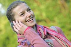 Ona un teléfono en el parque fotografía de archivo libre de regalías