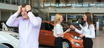 Żona zakup samochód, mężczyzna jest smutny obrazy royalty free
