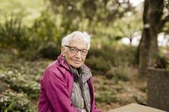 Onafhankelijk Bejaarde in de Parkzitting op Bank stock foto