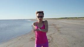 Onafhankelijke jonge vrouwenatleet die op strand lopen die vrouwelijke agent uitoefenen die opleiding op zonnige kustachtergrond  stock videobeelden