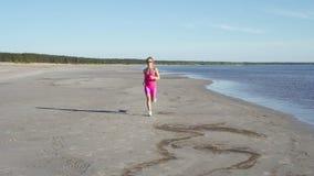 Onafhankelijke jonge vrouwenatleet die op strand lopen die vrouwelijke agent uitoefenen die opleiding op zonnige kustachtergrond  stock video