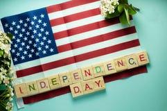 Onafhankelijkheidsdag het van letters voorzien op houten die kubussen op Amerikaanse vlag worden opgemaakt die dichtbij vertakt z royalty-vrije stock afbeelding