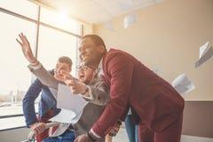 Onbedwingbaar team jonge vrolijke bedrijfsmensen in vrijetijdskleding die pret hebben terwijl het rennen bij bureau stoelen en he Royalty-vrije Stock Afbeelding