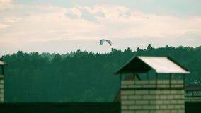 Onbekend aangedreven glijscherm die dichtbij de stad vliegen stock footage