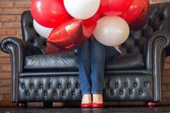 Onbekend die meisje in rode en witte heliumballons wordt verborgen op bank Kleurrijke ballons en vrouwenbenen in rode schoenen De stock foto
